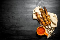 Shish kebab and tomato paste on the old fabric. Royalty Free Stock Photo