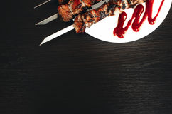 Shish kebab on white plate. Grilled pork meat on a white plate, a shish kebab from pork on black background Royalty Free Stock Image