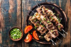 Shish kebab on wooden background. Grilled meat skewers, shish kebab on wooden background, top view Stock Photos