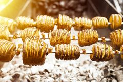 A shish kebab from yellow potatoes put on a skewer is fried on blue coals Royalty Free Stock Photos