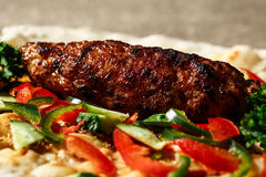 Shish kofte kebab. Shish kofte (kofta kebab) with vegetables and herbs on naan or lavash or pita flatbread Royalty Free Stock Image