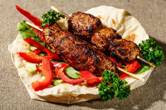 Shish kofte kebab. Shish kofte (kofta kebab) with vegetables and herbs on naan or lavash or pita flatbread Royalty Free Stock Photos