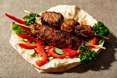 Shish kofte kebab. Shish kofte (kofta kebab) with vegetables and herbs served on naan or lavash or pita flatbread Stock Image