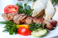 Shish pork kebab with greens and vegetables Stock Images