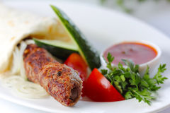 Shish pork kebab with greens and vegetables Royalty Free Stock Photos