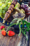 Shisha with fruity aroma. Hookah with fruit flavour on wooden table in vintage style stock image