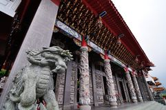 Shishi - Chinese imperial guardian lion statue at a pagoda temple. Shishi - a chinese guardian lion statue in front of a historical temple with a view of a tall Royalty Free Stock Photography