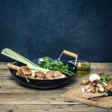 Shitake蘑菇为烹调在铁锅和斩肉板做准备 免版税库存照片