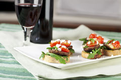 Shitake Mushroom Appetizers. Baked shitake mushrooms on toast with arugula, feta and cherry tomatoes Stock Photo
