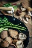Shitake mushroom prepare for cooking on wok and chopping block Royalty Free Stock Photos