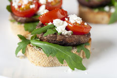 Shitake Mushroom Tapas on Toast. Shitake mushroom tapas with cherry tomatoes and crumbled  feta cheese Royalty Free Stock Photography