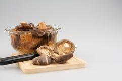 Shitake-Pilz, tränken Pilz in der Schüssel und im Messer auf hackendem Brett stockfotografie