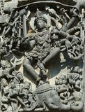 Shiva killing a demon Gajasura appearing in the guise of an elephant by dancing inside and piercing its skin; wall carving in Chan Stock Image