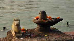 Shiva Linga en la estatua sagrada del toro en el banco del río Ganges
