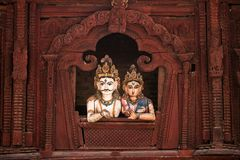 Shiva and Parvati wooden figures. In the window of Shiva Parvati Hindu temple at Durbar Square in Kathmandu, Nepal Stock Photography