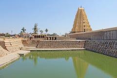 Shiva Virupaksha Temple and green pond, green water. Hampi, Karnataka, India. White yellow restored temple against the blue sky. Carving stone royalty free stock photo