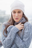 Shivering cute woman with winter clothes on posing Stock Photo