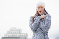 Shivering pretty woman with winter clothes on posing Stock Images