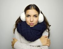 Shivering young woman with crossed arms being cold wearing earmuffs, sweater and scarf. Royalty Free Stock Image