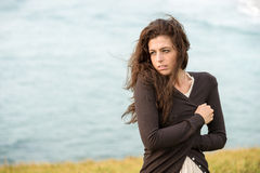Shivery sad woman. Sad shivery woman in brown sweater jacket hugging herself on late summer cold and windy day on sea background. Sadness, melancholia and heart Stock Photo