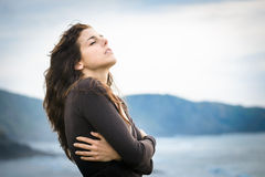 Shivery woman feeling the breeze. Sad woman shivering and feeling the sea breeze. Nostalgic and emotional female hugging herself and feeling low on cold late Stock Photo