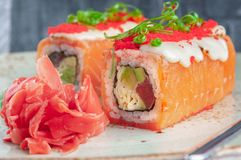 Shizu fusion roll. Wrapped in salmon, with the addition of mozzarella cheese and masago caviar. royalty free stock images