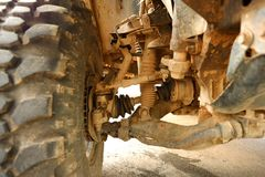 Shock Absorbers and Brake Pad in undercarriage of bigfoot car is stain of muddy soil. In the garage Royalty Free Stock Images