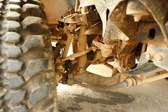Shock Absorbers and Brake Pad in undercarriage of bigfoot car is stain of muddy soil. In the garage Royalty Free Stock Photo