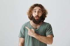 Shock content behind this corner. Indoor shot of amazed and stunned eastern male with beard and curly hair looking with. Popped eyes, saying wow and pointing stock photography