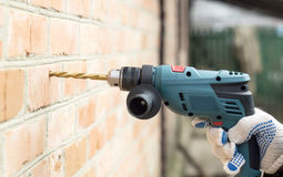 Shock Electric drill. Against the backdrop of a brick wall Royalty Free Stock Images