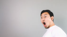 Shock face on empty copyspace. An asian man with white t-shirt and grey background Stock Photography