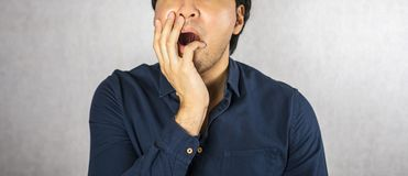 Shock gesture face with hand on grey background Royalty Free Stock Photos