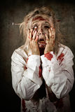 Shock horror. Surprised businesswoman zombie. Grunge portrait of a shocked bloody female business zombie with hands to decaying face and maggots crawling from Stock Photos