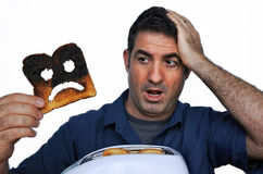 Shock man holds a burnt slice of toast Royalty Free Stock Image
