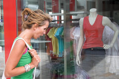Shock at the prices. Pretty blond woman looking shocked in the window of a clothing store Royalty Free Stock Image