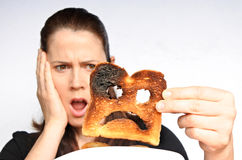 Shock woman holds a burnt slice of toast Stock Photo
