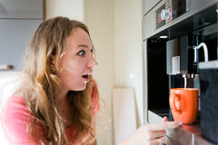 Shock young woman making coffee cup machine Stock Photo