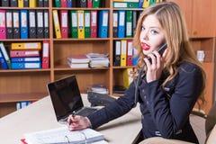 Shocked a étonné la femme parlant au téléphone dans le bureau Photo libre de droits