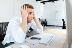 Shocked изумил молодой бизнесмена используя компьютер Стоковое фото RF