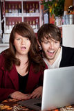 Shocked. Angry woman shocked with spouse over something on a laptop Stock Photography