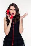Shocked使美丽的减速火箭的被称呼的妇女吃惊谈话在红色电话 免版税库存图片