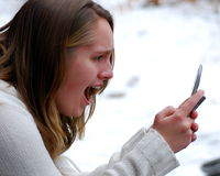 Shocked. A teen girl is shocked by a text message she has received Stock Photos