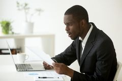 Shocked african-american businessman in suit surprised by readin. G mail paper letter holding notification sitting at workplace, amazed confused black employee Royalty Free Stock Photos