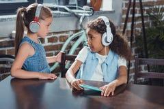 shocked african american girl in headphones looking at friend standing royalty free stock photos