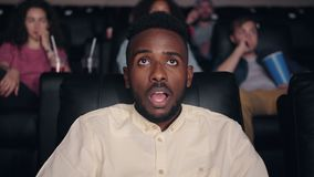Shocked African American man watching film in cinema with open mouth. Shocked African American man spectator is watching film in cinema with open mouth looking stock footage