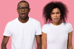 Shocked african couple looking at camera posing in studio royalty free stock images