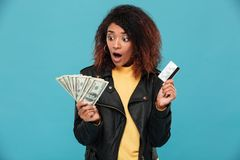 Shocked african woman in leather jacket holding credit card Royalty Free Stock Images