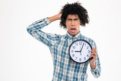 Shocked afro american man holding wall clock Royalty Free Stock Photo
