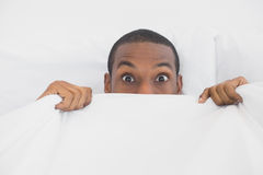 Shocked Afro man covering face with sheet in bed Royalty Free Stock Photos