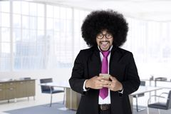 Shocked Afro man looking his mobile phone. Portrait of shocked Afro man with curly hair looking his mobile phone, shot in the office Stock Image